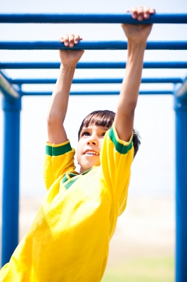 kid in yellow shirt hanging from monkey bars